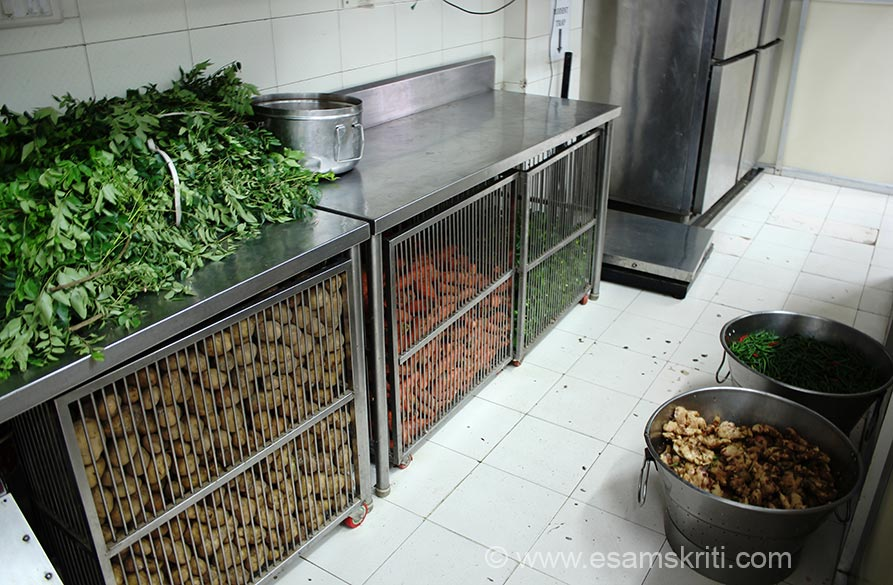 """Kitchen is huge rectangle shape. Left side is kitchen that you saw. Right is veggie and grain storage area + small office. U see potatoes, carrots, ginger, vegetable etc. Far end of pic is a Cold Storage. """"When the Government of India launched a strategic program in 1995 called the Midday Meal Scheme to fight two of the most pressing problems of India – hunger and illiteracy, ISKCON Food Relief Foundation saw a great opportunity for providing children with the right nutrition to support their education"""". So foundation was set up in 2004."""