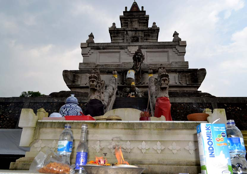 A horizontal close up view of the shrine. Milk tetrapacks and plastic bottles do not make good viewing.