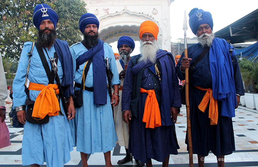 As I was about to walk into the temple saw these men in warrior dress. We have analysed their dress and arms later. Second person left to right took some convincing to be clicked.