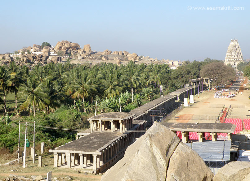 Extreme right u can see gopuram of Virupaksha temple. The road in the centre is Hampi market. The red chairs that u see were for Hampi Festival program. The boulders that u see on the left of the pic are 