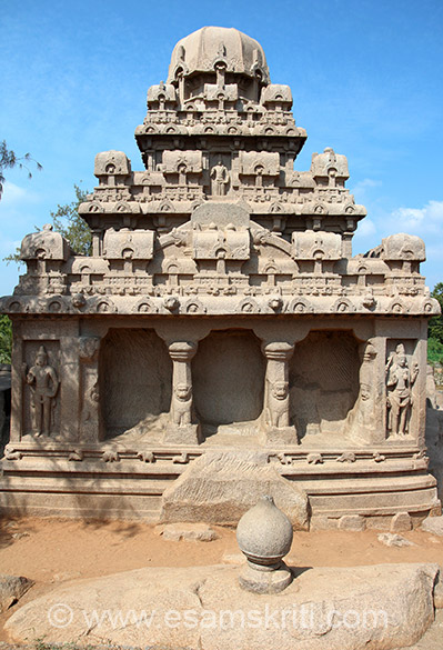 Back side view of Dharmaraja-ratha.  The temple is a pyramidal structure with a square base. The upper part consists of a series of diminishing storeys, with having a row of pavilions above a row of kudu (chaitya-windows) arranged immediately above brackets of pilasters. They divide the actual portion of the temple into niches with carved images. In the lower tier, there are 4 corner blocks each with 2 panels. In centre of are 2 pillars and pilasters supported on squatting lions.