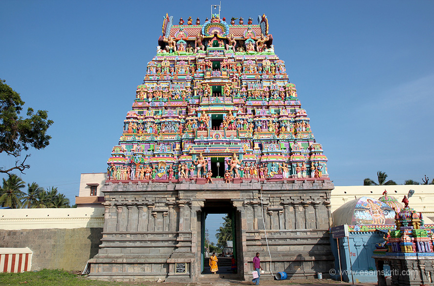 "Rear view of main gopuram. ""The presiding female deity's shrine is also facing east and She is known as Yazhinum Iniya Mozhiyal in Tamil which means that the voice of the Goddess is sweeter and melodious than the sound of Veena (a musical instrument). Hence it is pertinent to note that the Shrine for Saraswathi in this temple is different in the sense that Goddess Saraswathi is seen here without her Veena in her laps as normally seen everywhere."" To read about temple tradition and see pictures of deities <a href=""http://kumbakonamtemples.in/maraikattunathar-temple-vedaranyam.html