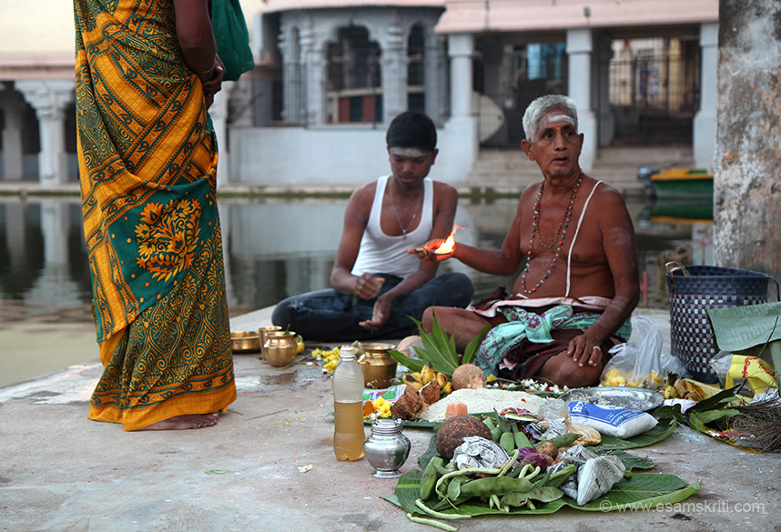 "On banks of water tank Pandit performing ceremony. ""Sapta Vitanka Shrines refer to seven temples in the Chola kingdom enshrining images of Thiyagaraja brought to earth by Mucukunda Chakravarti.