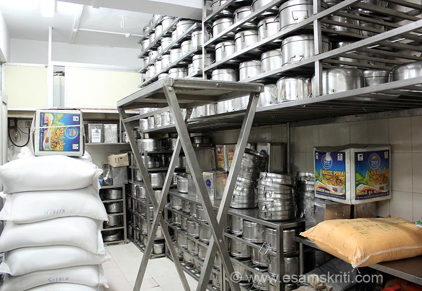 """Storage area where on left is rice in bags and right are containers in which food is sent to schools. """"The Midday Meal Project is being implemented under the name of ``annamrita`` meaning food as pure as nectar."""" When you think of nutritious food you think what a mother serves to her child and ie what annamrita stands for. Food cooked by your Mother is always tastier because  it has lots of love in it. I saw a similar bhavna or feeling of love in the eyes of all those who worked in this kitchen. The ambience is spiritual and the kitchen hi-tech. Each kitchen cost app Rs 3.5 crs. Rental for premises and overheads are extra."""