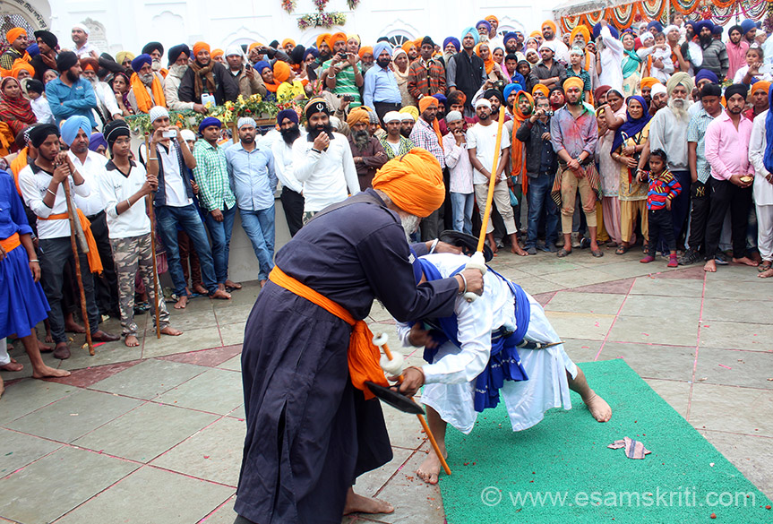Warrior in white, after a mock fight, pays respects to the senior in blue. Gatka is a style of fighting between 2 or more practitioners, with wooden sticks intended to simulate swords. After the Second Anglo Sikh War 1848-49 and British Raj, the Sikh martial practioners suffered greatly. British ordered effective disarment of the Sikh community. Nihangs, regarded as keepers of keepers of Sikh traditions, were killed in large nos by the British. It is because the Sikhs supported the British during the 1857 Mutiny that restrictions on fighting were relaxed.The old method of sword training was replaced with sticks.