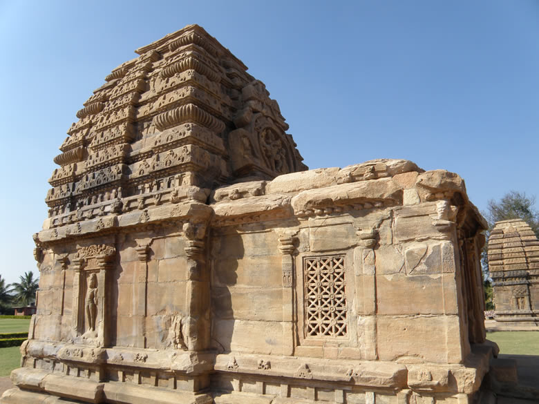 Jambulinga Temple probably built in the middle of the 7th century, in the Nagara style. The façade of the vimana above the entrance shows Dancing Shiva with Parvati and Nandi watching. In the Northern style from above the square (nagara) garbha-griha rises a square tall superstructure (shikhara) of curvilinear profile (rekha) divided horizontally but distinctly into 3 or 4 or 5 zones (bhumi). It is crowned with a cushion like circular, flattish, solid member releived on the edge into series of parrallel sharp vertical ridges allround looking like a gadroom (amalaka). On it are a pot (kalasha) and needle like staff (suchi) one on the other. In pic no 7 you can see the amalaka and kalash. In the front of Sikhara is a sculptural replica of the deity enshrined in the garbha-griha which you can see in the center of the picture.