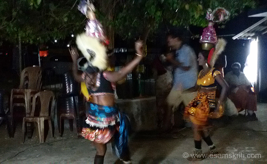 Village girls dancing. Wearing skirts, ghungroos, brass bowl on head etc. Enjoying themselves and villagers too, to some hummable music.