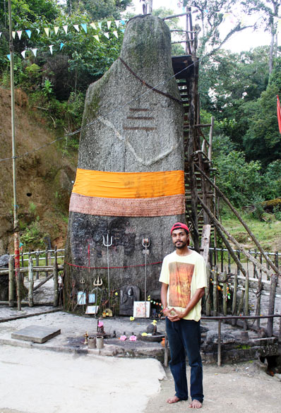 There is a huge open area in which the Shiva Lingam stands and is surrounded by forests on all sides. A vertical view of the shivalinga with my driver Chandan Barua in front. He drove over