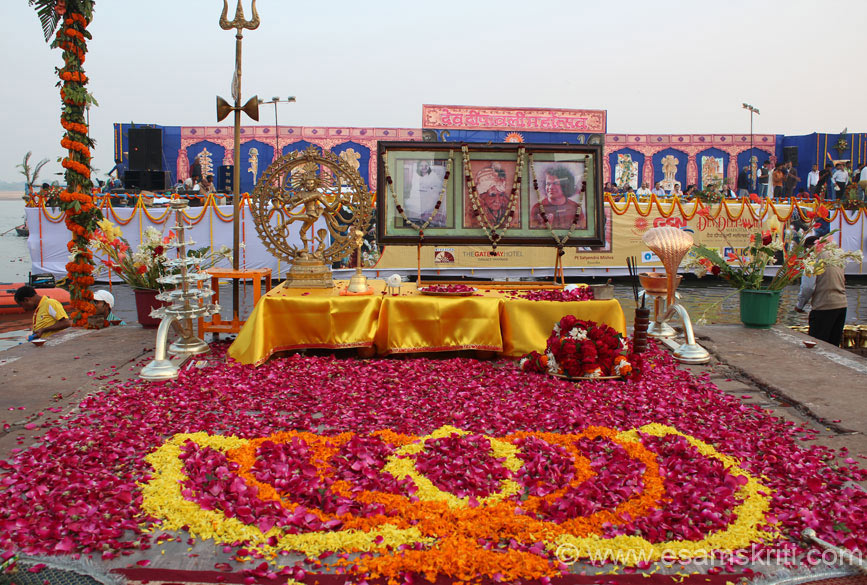 Centre marigold flowers in the form of a lotus with roses all around. On table is Nataraja and pictures of Satya Sai Baba amongst others with stage in the background. The arrangements