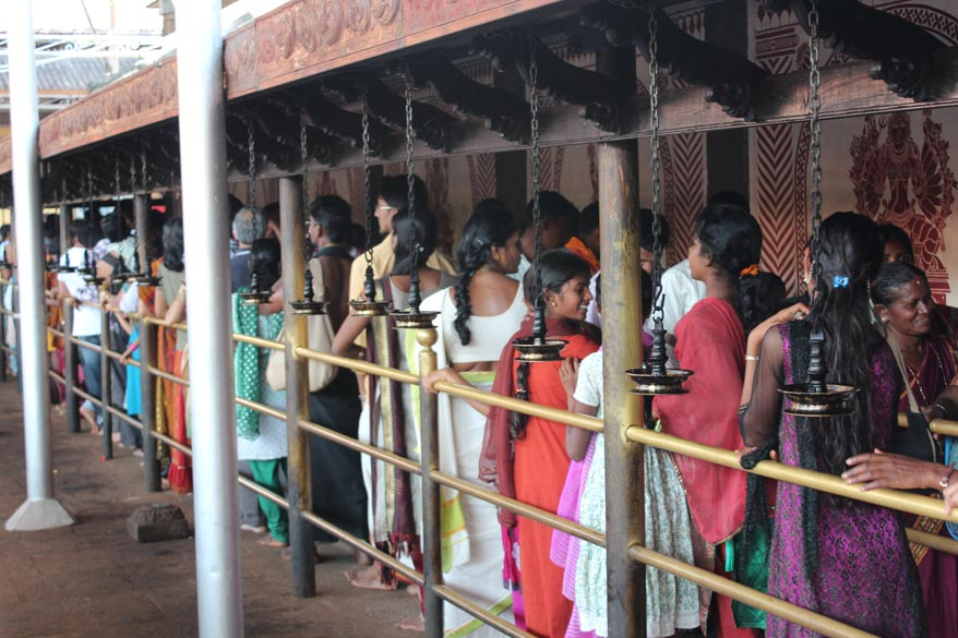 "All round the temple wall devotees stood in que like this. In front u can see a series of brass lamps or deepas. ""The history of idol installation at Kollur Mookambika temple is nearly 1200 years