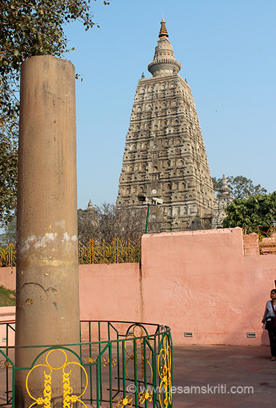 "The Ashoka Pillar in temple tower behind. This one is situated close to the Mucalinda Lake. (Lotus tank). ""A wandering Sanyasi (Saivite monk) named Mahant Ghamdani Giri arrived in