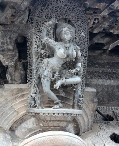 Dancing on a single leg - Natya Mayuri. Right of pic next to maiden head u can see a small lizard, above that is a fruit on which is a fly. Architectural design and such minute work is called 