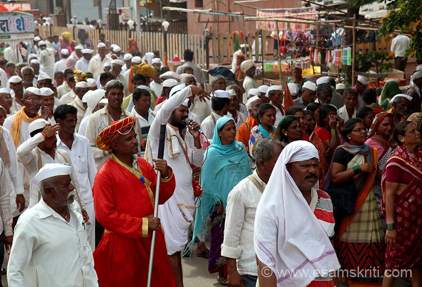 "U see group in Pandharpur proceeding to Vitthala Temple. Every group has a person, with red dress as you see, who controls the group members as they walk to Pandharpur. He also has a whistle ie used to control crowds. For a brief introduction to Vitthala and the Varkari Movement <a href=""http://www.rkmpune.org/readings/vithoba.html"" target=""_blank"">Click here</a>"