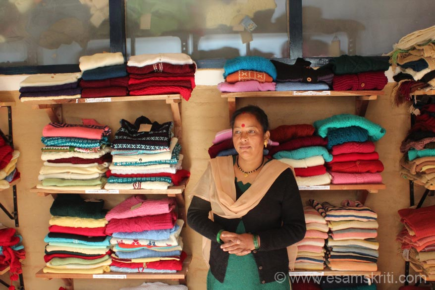 U see Basanti with some woollen products. She and hundreds of other ladies are shareholders in the company that runs UMANG. To read about Grassroots work in Community Forestry <a target=_blank href=http://www.grassrootsindia.com/communityforestry.html>Click here</a>