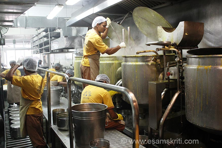Right to left are 4 cooking vessels called Cauldron. Cooks stand on an platform as you see. The menu on day of visit was Khichdi for which ingredients were-water boils, add veggies/lentils, add masalas thru tadka, mixing (as you see a devotess doing), boiling, release valve, fill in steel utensils, seal and send in van for delivery.