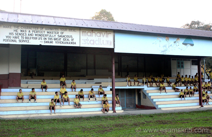 "Post Yoga students run round a huge playground and then sit on this stand in Mahavir Stadium. Notice the words of Swamiji on Mahavir and Hanumanji with hill Sanjeevani. ""When Lakshmana fell unconscious, near death, hit by an arrow from Ravana's son Meghnad, Hanuman approached the Lankan Royal Physician Sushena for advice. Sushena asked Hanuman to rush to Dronagiri Hills and fetch 4 plants. Hanuman, not able pick the 4 from the multitude, brought back the entire hill."" Of the 4 Sanjeevani is said to be the most imp since it brought back Lakshmana to life. To read more <a href = ""http://www.thehindu.com/sci-tech/science/in-search-of-the-sanjeevani-plant-of-ramayana/article17925.ece"" target = ""_blank"" > Click Here </a>"