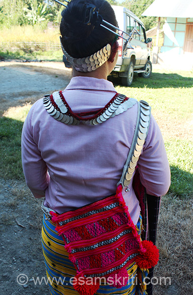 Note the bag, silver coins and her hair do. She belonged to the Mizo Mishmi tribe.
