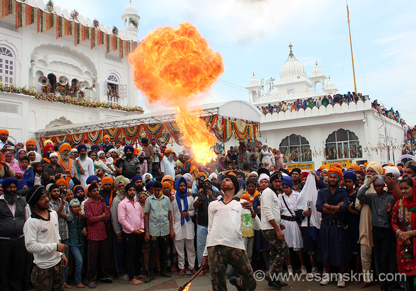 At Anandpur Sahib during Hola Mohalla festival - young man has a stick in hand with fire lit at top end. From a bottle he fills his mouth with Oil, then with full force throws out the oil on the flame to get what you see. Many many young boys did this and got wow looks from all who had gathered.
