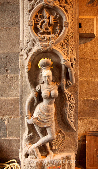 At main entrance door, sculptures on both sides. Lower level is lady think with snake in hand. Above is a 8 handed man with weapon in hand. The temple has seven prakaras (inner walls) and nine gopurams.