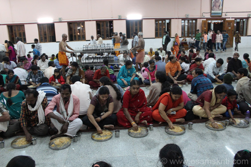 A view of the devotees enjoying meals. In the centre u see plates ka trolley.