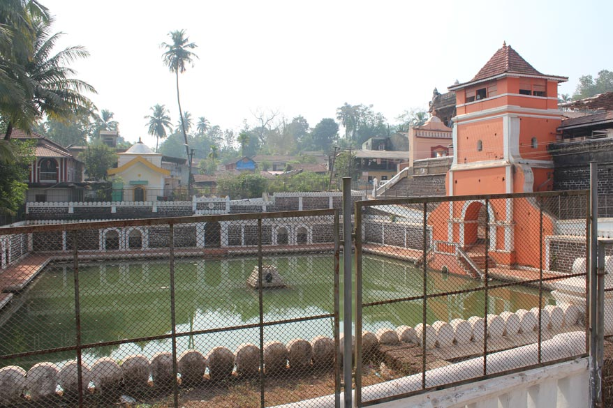 Water tank outside the temple. In centre is tulsi plant, in front are steps. It is closed.