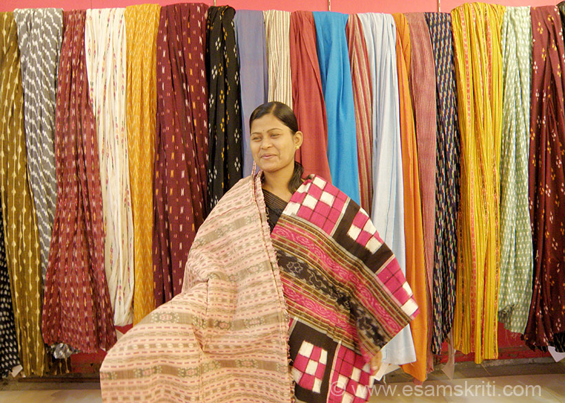 "Cotton sarees displayed by a salesgirl. To know about Origin of Indian Saree. <a href=""http://www.esamskriti.com/essay-chapters/THE-ORIGIN-OF-THE-SAREE-1.aspx"" target=""_blank"">Click here</a>"