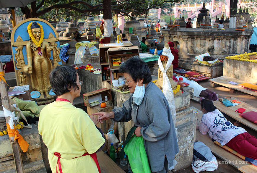 This gives you an idea of how the devotees, monks live inside the temple complex. You can see Buddha image, flowers, fruits, water bottle and on right  a devotee praying lying on wooden