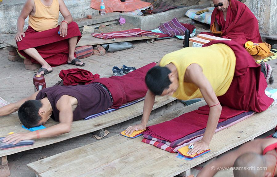 The Buddhist monks here are doing their prostrations before the Buddha. By venerating the Buddha and his teachings through these prostrations, one seeks to awaken compassion in all sentient