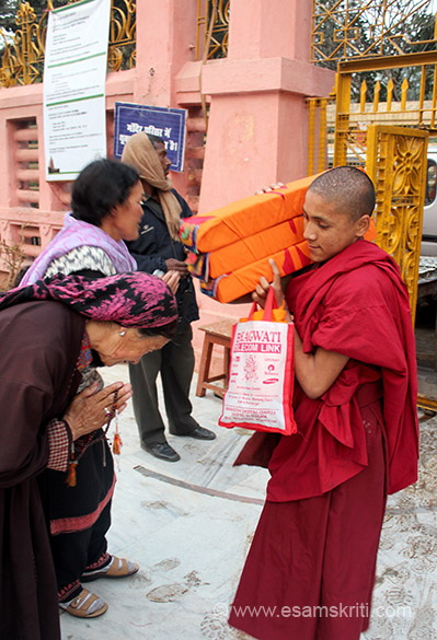 Young Bhutanese monks taking sacred Buddhist texts from the car and to their class. Devotees bow down in respect to them.