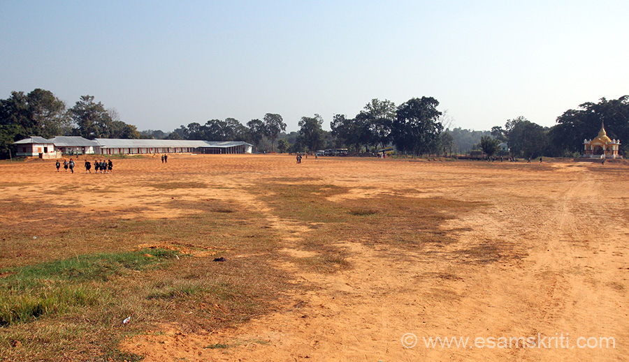 "School ground. Far end left is pagoda, centre is school buses and school. Happy to see so many boys and girls in the school. People who live in big cities wonder what facilities would exist in smaller places like this but honestly it is not so bad. Townies want too much of comfort. To see pics of Tribal Museum Tripura  <a href=""http://www.esamskriti.com/photo-detail/Tribal-Museum-Agartala.aspx"" target=""_blank"">Click here</a>"
