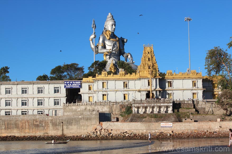 Early morning sun rays on Murdeshwar mandir and Lord Shiva. To left of temple is blue sign board. Just below that is the entrance to the dining hall. The golden color pole in front of temple
