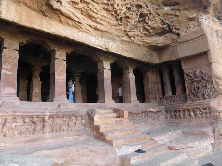 A closer view of the cave entrance. Right of pic is the 18 armed dancing Shiva demonstrating Bharata-natyam postures. The pillars that separate the verandah  from the hall have fluted upper parts with cushion capitals. Apart from bead-garlands and other finely carved decorations the pillar faces have smaller depictions of iha-mrigas (dream animals). Observe closely pillar design of external and verandah is different.