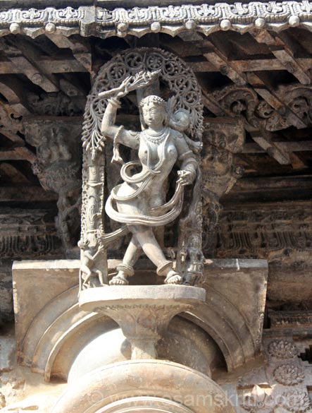 Devangana image. Holds a flower in her hand. Bottom left of pic is a monkey who is pulling the saree of a lady. Figure in east wall.