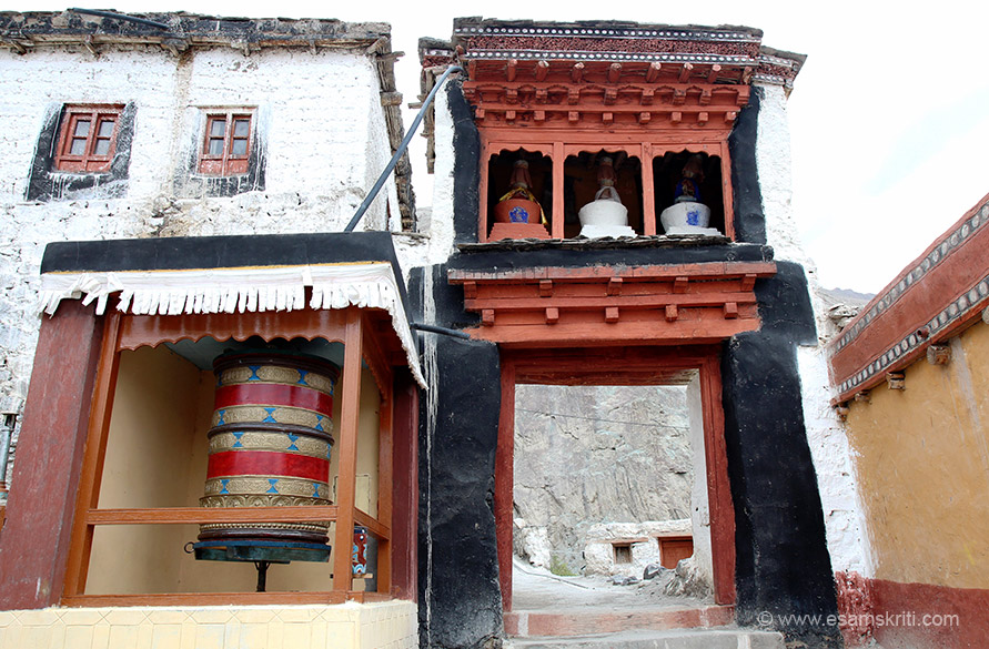 Entrance to Gompa. On left is prayer wheel. It has an auspicious decorative border. Red is considered auspicious in Buddhism and is often used on entrances in combination with blue and yellow.