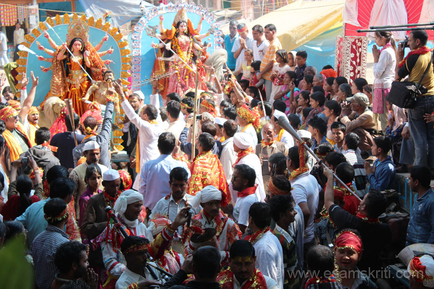 Various images of Ma being taken in the procession. Men and women both dancing, crowds in high spirits and happy.