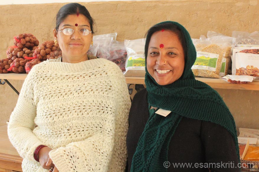 Close up of two salesperson and shareholders left to right are Indira and Basanti. They are displaying some of the woollen products made by UMANG. Indira is wearing a shawl cum 