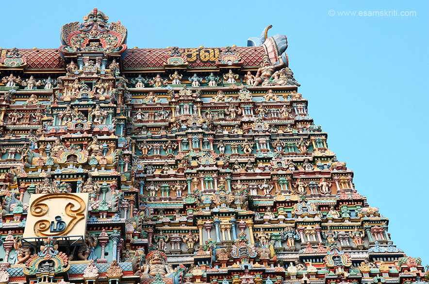 "East gopuram right side top. Centre of gopuram large face like thing is Kirti Mukha - to keep away evil spirits. ""Gopurams covered from top to bottom with multi-colored images of celestial 