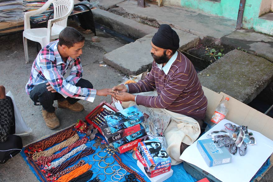 From Pithoragarh went to Dharchula enroute to Narayan Ashram. In the Dharchula market clicked this pic. Man advising client to wear a particular type of ring to help control his temper.