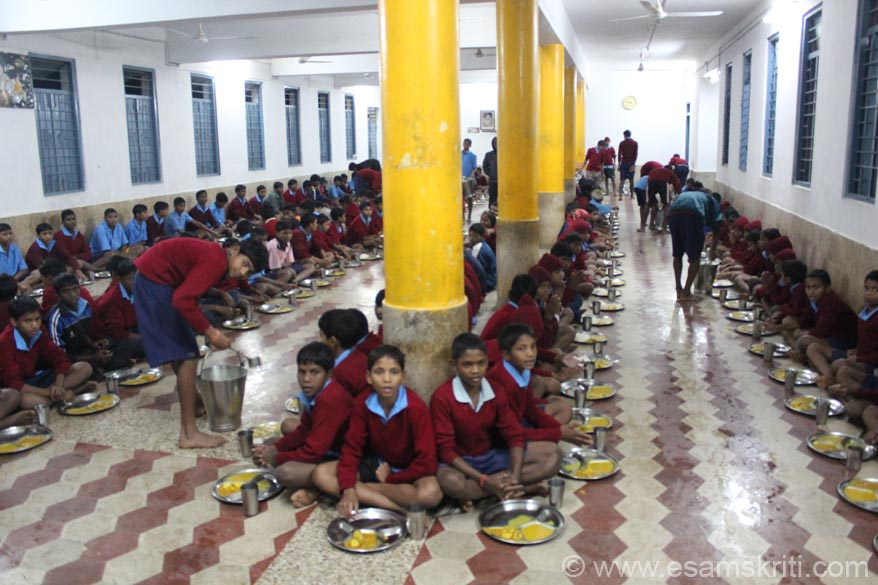 This is Madhyamik Niwas. U see dining hall for students up to 8th standard. Every child is given a plate, spoon and glass. He has to wash it himself before and after using. Food is served by 