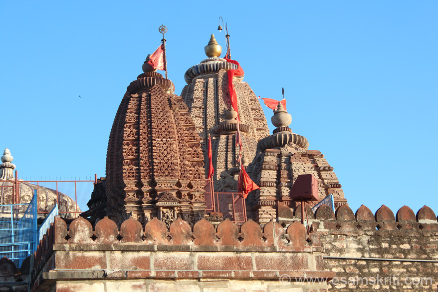 A side view of the shikharas of various temples with the main temple shikhara in the centre. Note the fort type wall. Temple is made of stone, mortar.