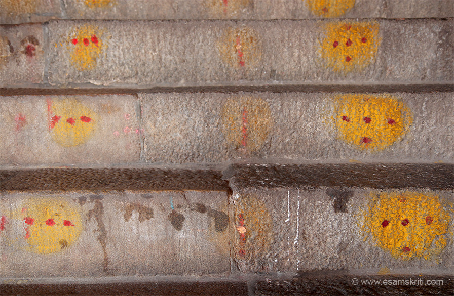 When devotees take a vow they clean the steps with water and then apply haldi kum kum on step as you see. It helps to reduce one``s ego as it involves touching the Paada duli of devotees. 
