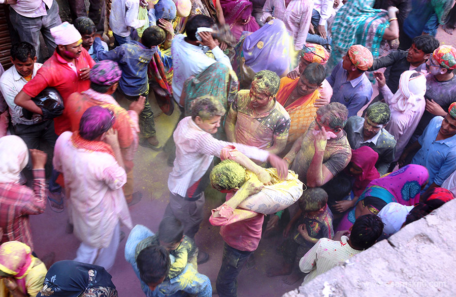 """Boy walks in with sack full of color. People put their hand in the bag and throw color all over. """"Thus the tradition of applying colour on one's beloved is being religiously followed till date."""""""