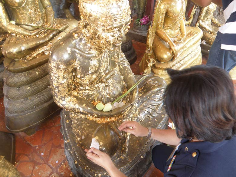 A close up of a Thai lady putting a gold piece of paper on the image. Am told even the Burmese do that.