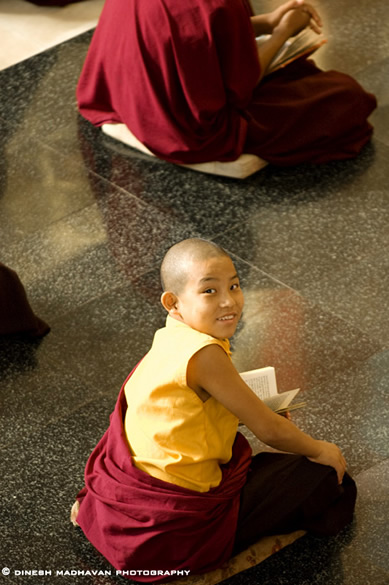 A young monk disturbed by my photography during his teaching session.