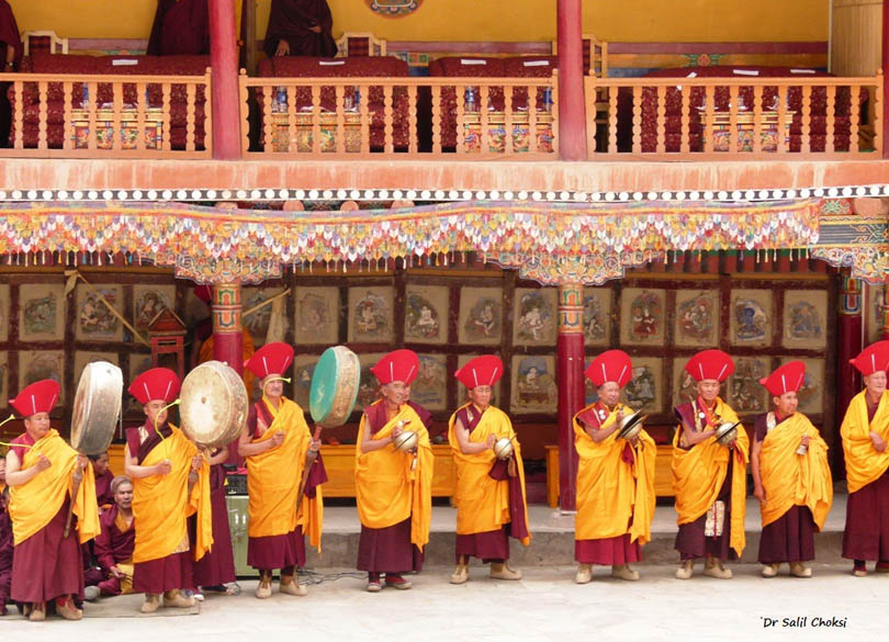 Lama musicians with cymbals, drums, and unwieldy trumpets.