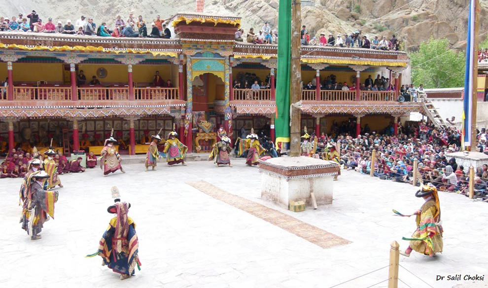 The festival takes place in the rectangular courtyard in front of the main door of the Monastery. The space is wide & open apart from two raised square platforms, three feet high, with a sacred pole in the centre. On a raised dais decorated with a richly cushioned seat, is placed a small, finely painted table on which are displayed ceremonial items – cups full of holy water, uncooked rice, tormas made of dough and butter and incense sticks.