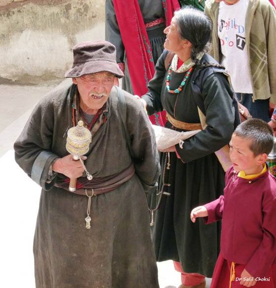 A wizened Ladakhi with his prayer wheel. Known as Mane Laro, the hand prayer wheel is of Tibetan origin. The mantra ``Om Mane Padme Hum`` is inscribed on the outer wall of the prayer wheel. Inside the wheel is a scroll in which the mantra is written many times. The wheel is whirled clockwise, activating the mantra with each rotation.