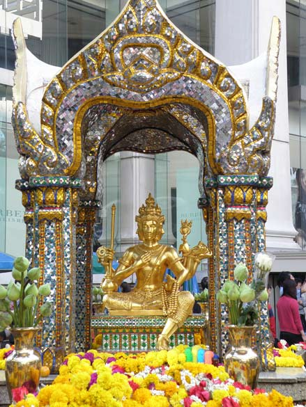 Erawan shrine ie close to Central World, Chidlam skytrain station . It is a Lord Brahma shrine. Board says it is Thao Maha Brahma. Thai Buddhist tradition associates Lord Brahma with creation. The 4 faces of Brahma represent the Four Divine States of Mind.Brahma has four arms, he holds a lotus flower, his sceptre, his bow parivita, a string of beads, a bowl containing the holy water and the Vedas. He has four heads and is therefore called Chaturanana or Chaturmukha. His vehicle is the swan or goose, the symbol of knowledge. He is thus said to be riding on the swan (hansa-vahana). Lord Brahma known as Phra Phrom in Thailand.