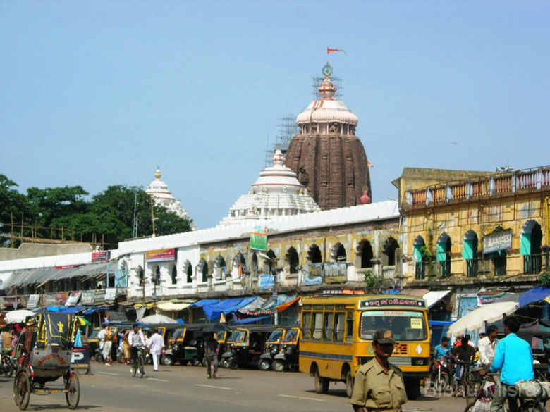 The view of the temple from the Bada Danda i.e. the Grand Road along which the chariots are pulled on the day of the Ratha Yatra. The current temple was built in the 11th century on the ruins of a previous one, by the Eastern Ganga dynasty King Anantavarman Chodaganga Deva. The temple spire rises to 214 feet (65 m) above the inner sanctum where the deities reside. On top of the temple is a eight-spoked wheel of Vishnu called the ``Srichakra`` or ``Nilachakra``.