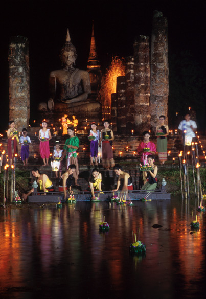 This looks like festival of light celebrations at Sukhothai Historical Park. Prior to setting their krathong afloat, people place in it a lighted candle, incense sticks, flowers, a coin and some food offerings. They make a silent prayer of thanks for the water received, a request for forgiveness for wrongs done, and a wish for the fulfillment of a personal dream. You saw Thai women doing that in pic no 1 and this one.
